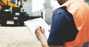 Man At A Construction Site Writing For WorkCover NSW