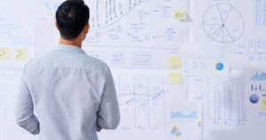 Man Looking At Graphs Cut Costs Or Keep Staff