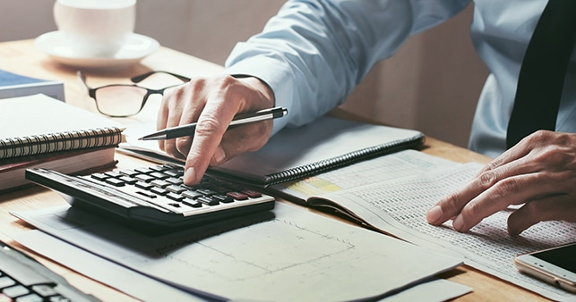 Man Using Calculator Avoiding Underpayments