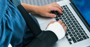 Person With Broken Arm In Sling Typing On A Laptop