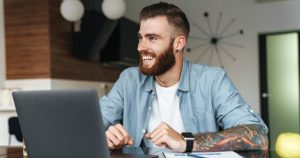 Bearded And Tattooed Man Smiles While Working On Laptop