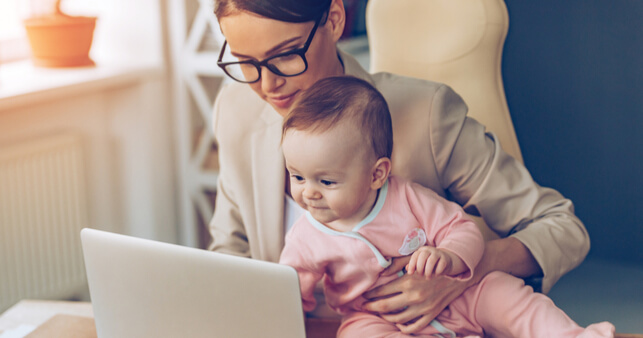 Woman In Glasses Holding Baby In Pink Onesie While Typing At Laptop