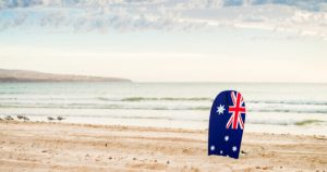 Boogie Board With Australian Flag Stuck In Sand At Beach
