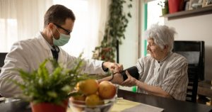 aged care nurse with paid pandemic leave helps patient